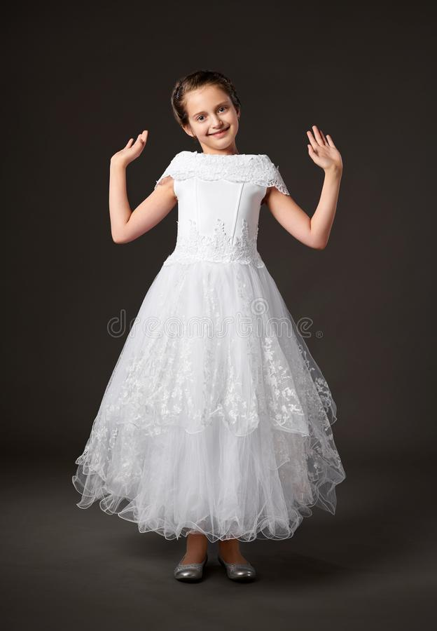 Little girl is dressed in a white ball gown, dark background stock photography