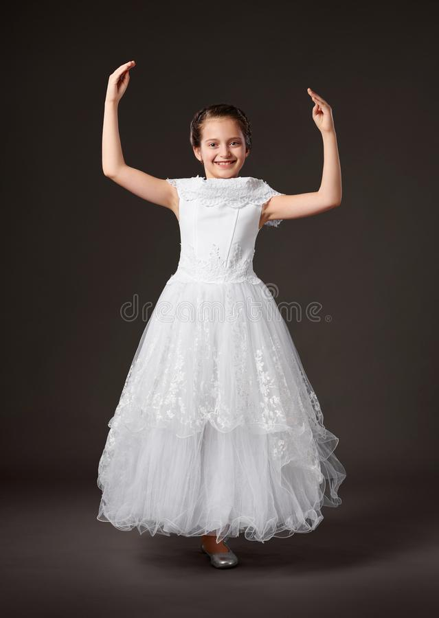 Little girl is dressed in a white ball gown, dark background stock images