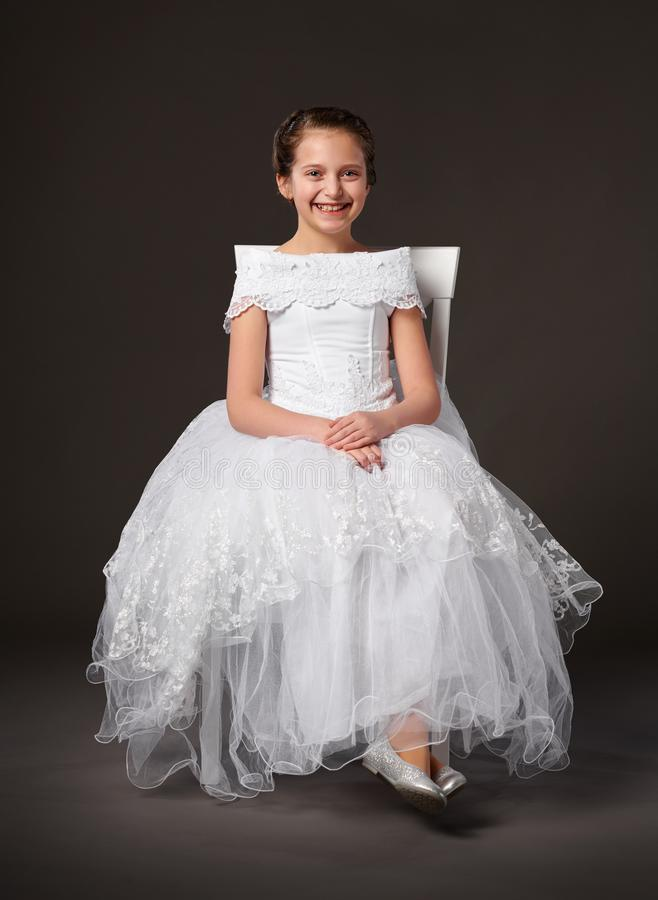 Little girl dressed in a white ball gown and sitting on the chair, dark background stock photos