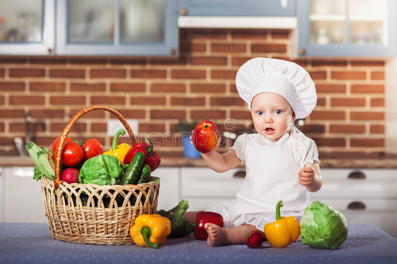 Little girl dressed in white chef hat and apron, sits among vegetables and holds an apple. stock photos
