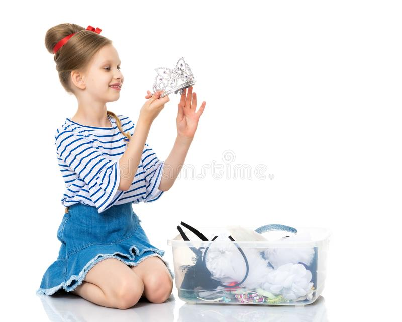 The little girl dresses up. A little girl tries on various decorations. She dresses up for the holiday. Use it for princess concept and dressing. Isolated on stock photos