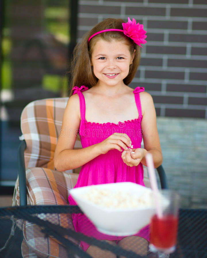 Little girl is drinking cherry juice. And eating popcorn while sitting on terrace royalty free stock photo
