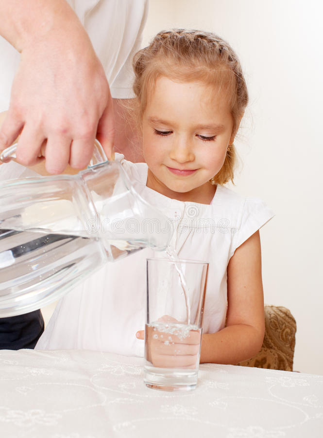 Download Little girl drinking water stock photo. Image of pitcher - 26022886