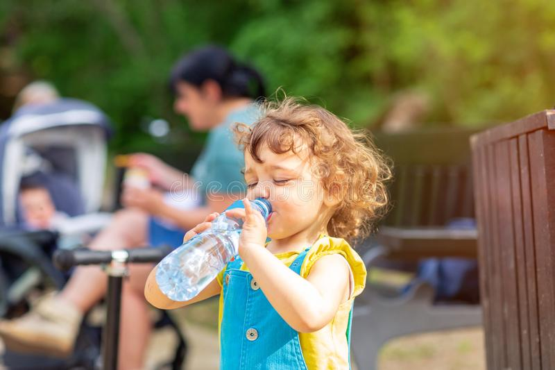 Little girl drinking water from the bottle in park. Little cute girl drinking water from the bottle in park royalty free stock images