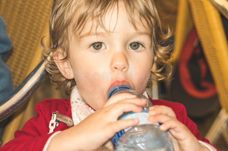 Little girl drinking water from a plastic bottle stock photography