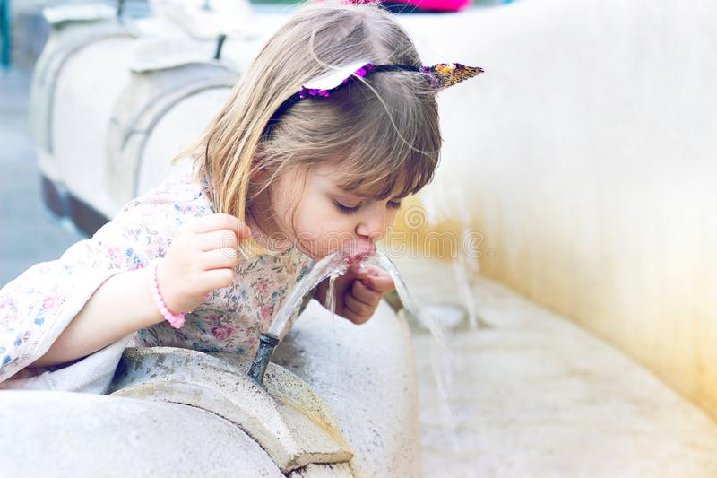 Little girl drinking water on public fountain. Cute little girl drinking water on public fountain stock image