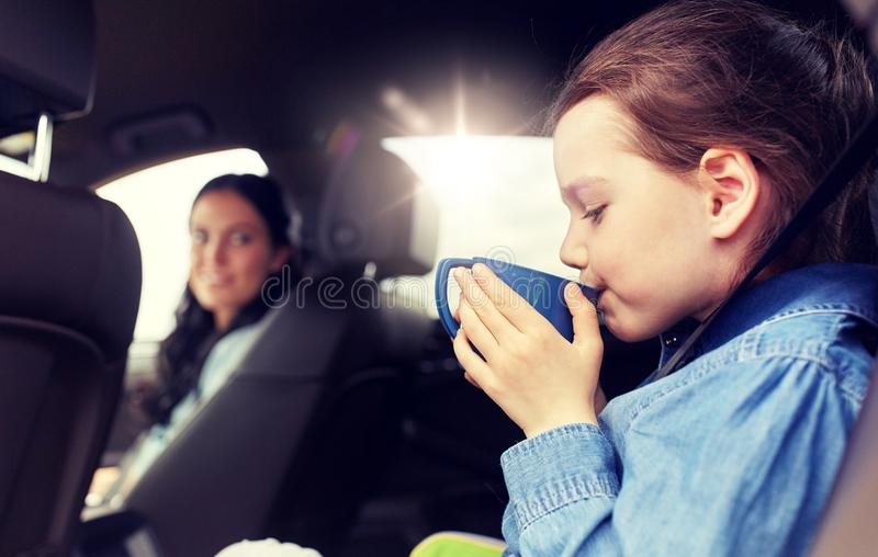 Little girl driving in car and drinking from cup royalty free stock photo