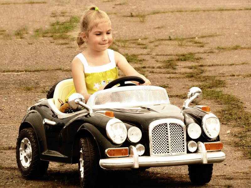 Little girl driving a car on the road stock images