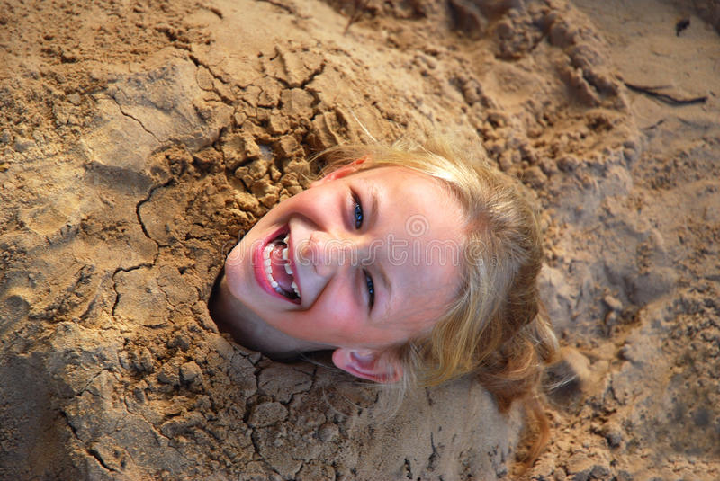 Little girl dug into sand. Outdoor head portrait of a cute little blond Caucasian laughing girl child with blue eyes with body buried in sand royalty free stock photos