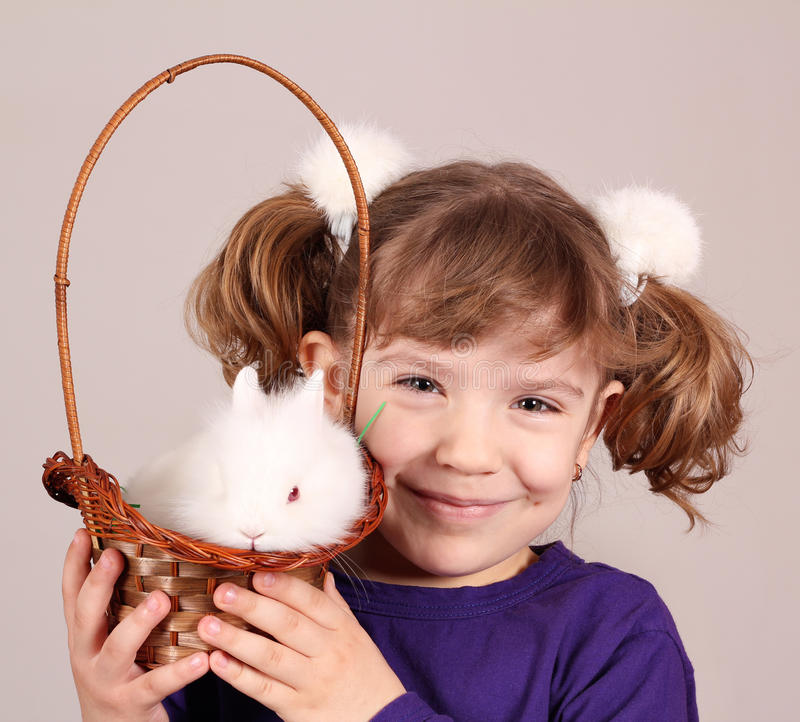 Little girl with dwarf bunny pet. Happy little girl with dwarf bunny pet stock photo