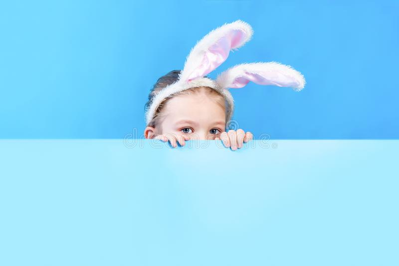 A little girl with ears from a white rabbit costume peeking out from behind a sheet of blue cardboard. Copy space royalty free stock photos