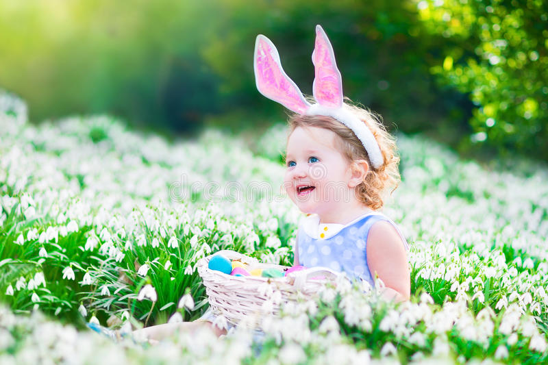 Little girl at Easter egg hunt. Adorable curly toddler girl wearing bunny ears playing with Easter eggs in a white basket sitting in a sunny garden with first