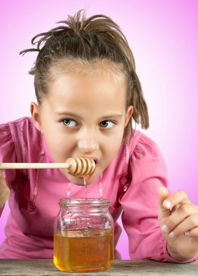 Little girl eat honey royalty free stock image