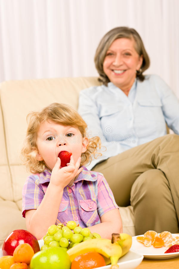 Little Girl Eat Strawberry Fruit With Grandmother Stock Photos