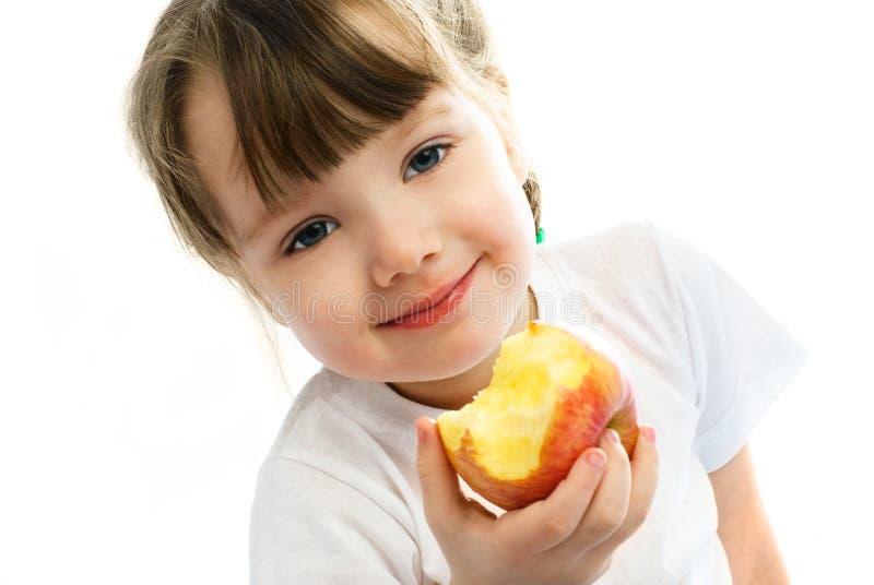Little girl eating an apple stock photos