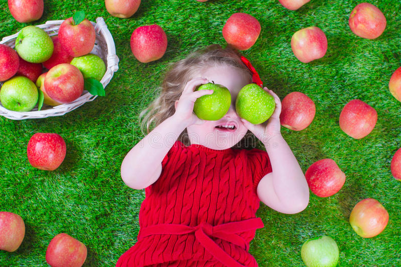 Little girl eating apples. Child eating apple. Little girl playing peek a boo holding fresh ripe apples. Kids eating snack relaxing on a lawn. Children summer stock photo