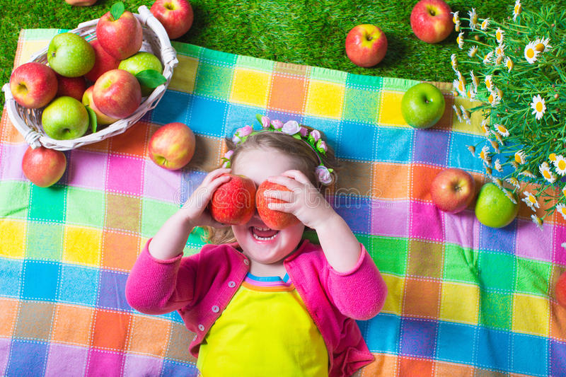 Little girl eating apples. Child eating apple. Little girl playing peek a boo holding fresh ripe apples. Kids eating snack relaxing on a lawn. Children summer stock images