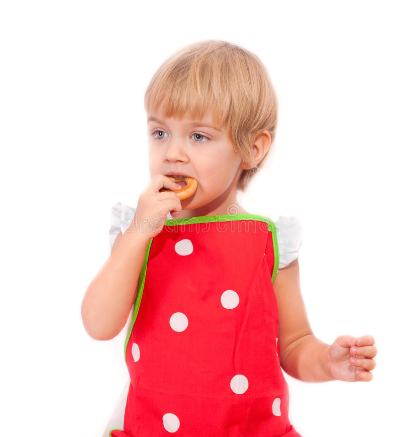 Little girl eating bagel royalty free stock photography
