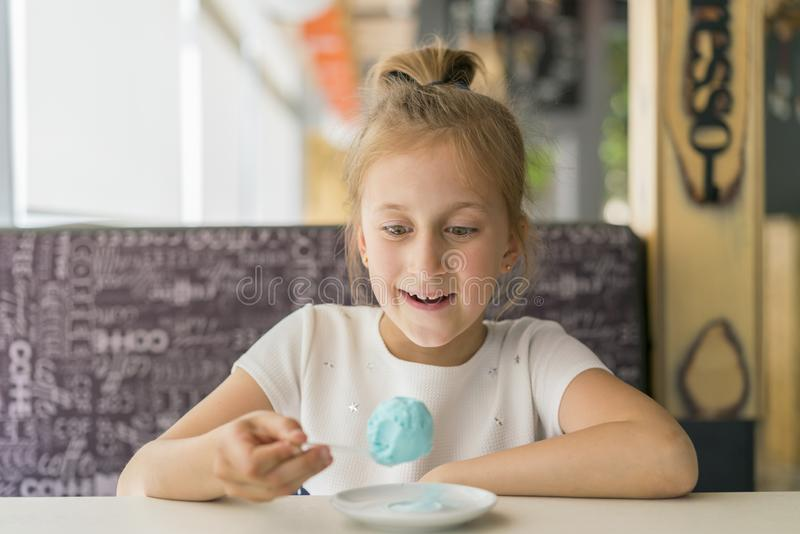 Little girl eating blue ice cream in a cafe. Girl delighted with ice cream. Adorable little girl eating ice cream at summer.  stock photos