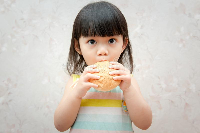 Little girl is eating bread stock images