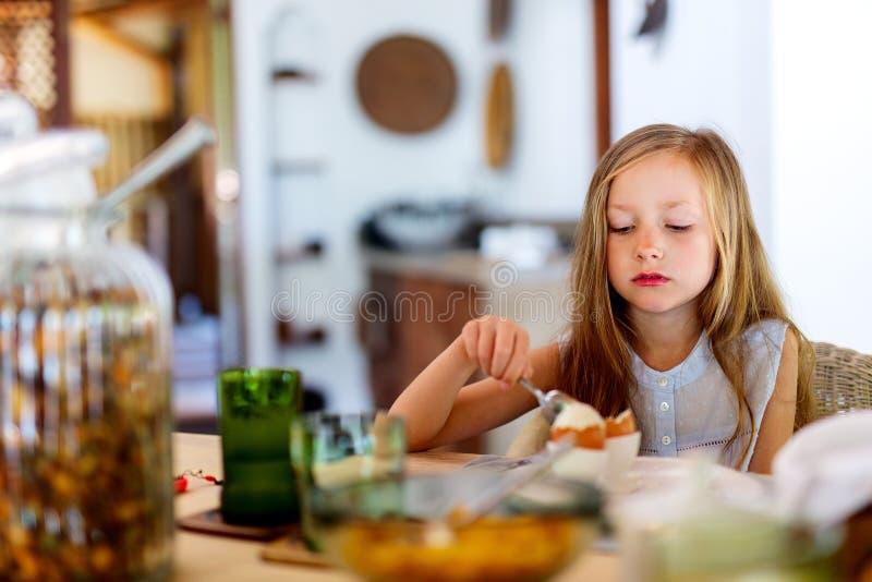 Little girl eating breakfast. Adorable little girl eating boiled egg for a breakfast in restaurant stock image