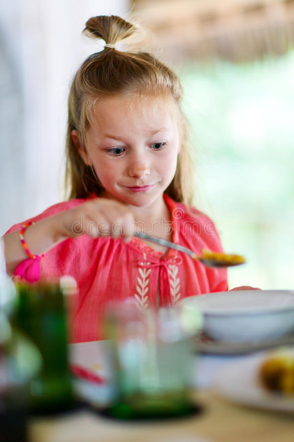 Little girl eating breakfast. Adorable little girl eating cereal with milk for breakfast in restaurant or at home stock photography