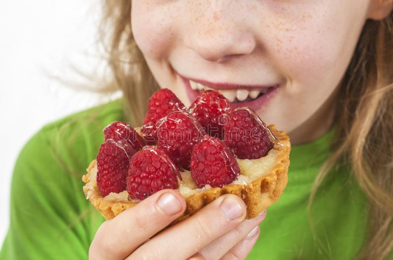 Little girl eating cakes with fruits. Little girl eating cakes with sweet fruits stock image