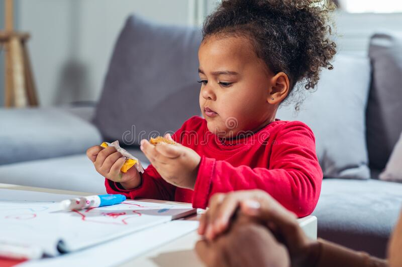Little girl eating candies at home. stock photography