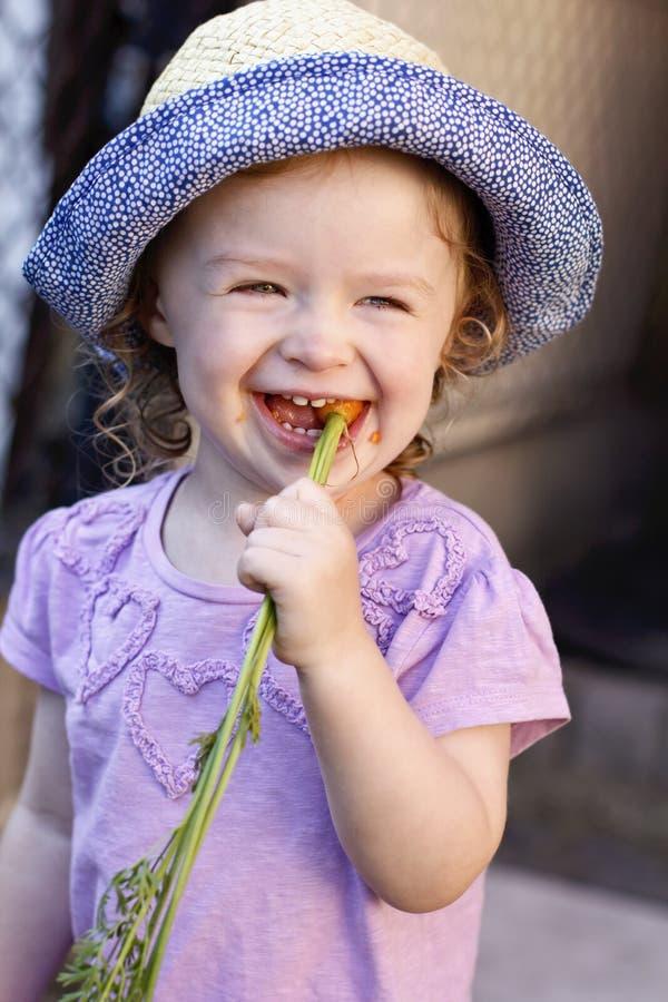 Little girl eating carrot