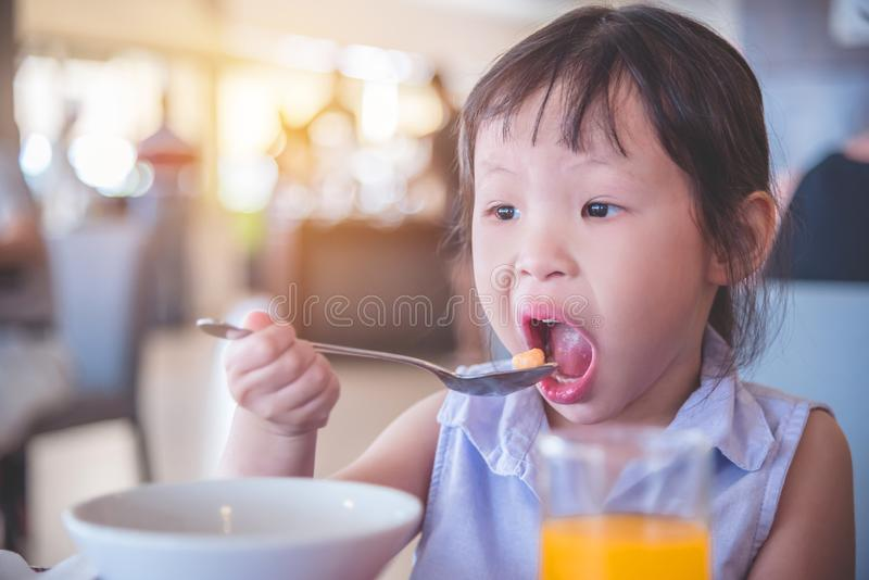 Little girl eating cereal for breakfast royalty free stock photography