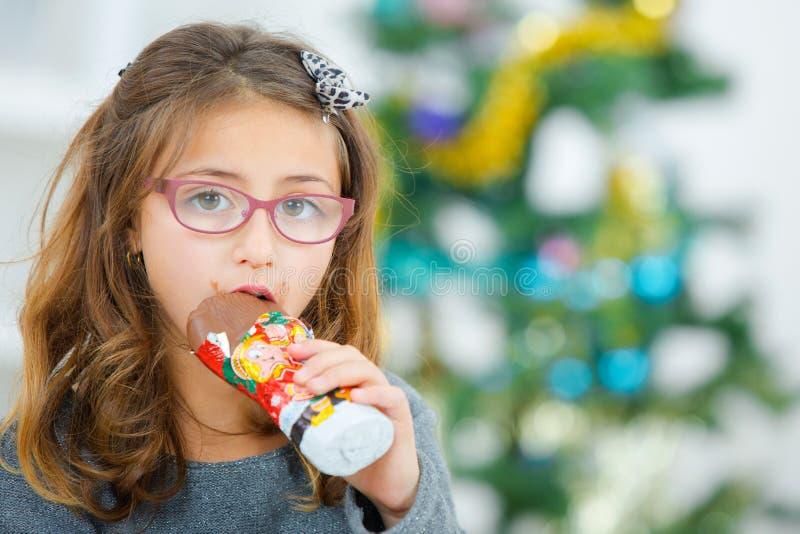 Little girl eating chocolate at Christmas stock photography