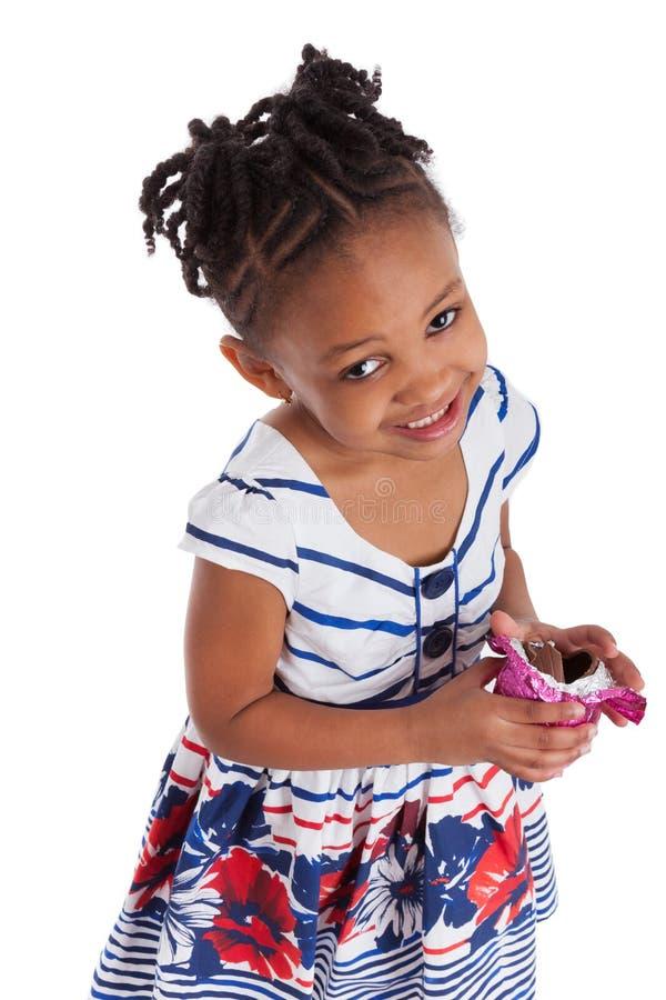 Little girl eating chocolate easter egg stock photo