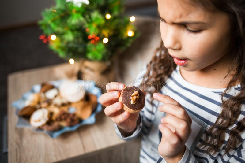 Little girl eating Christmas cookies. stock images