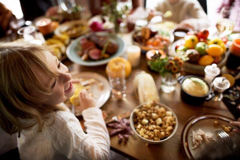 Little Girl Eating Corn Thanksgiving Celebration Concept royalty free stock image