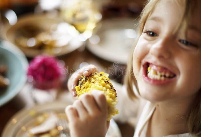 Little Girl Eating Corn Thanksgiving Celebration Concept.  stock photo