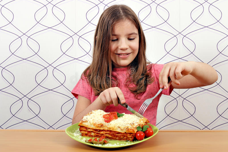 Little girl eating delicious lasagne stock photo
