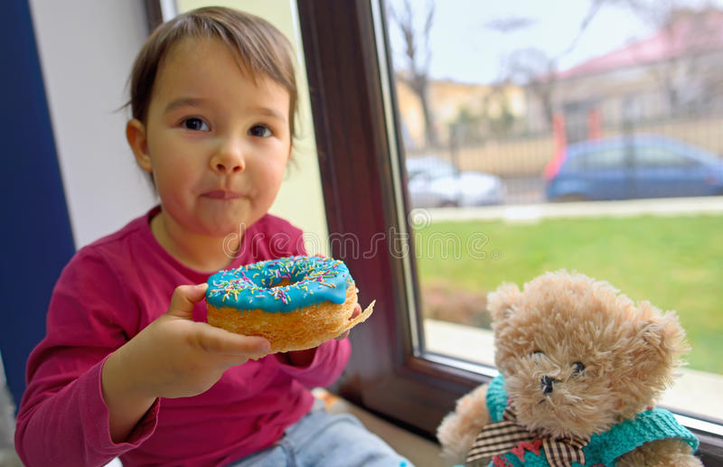 Little girl eating donuts. With her toy friend stock photos