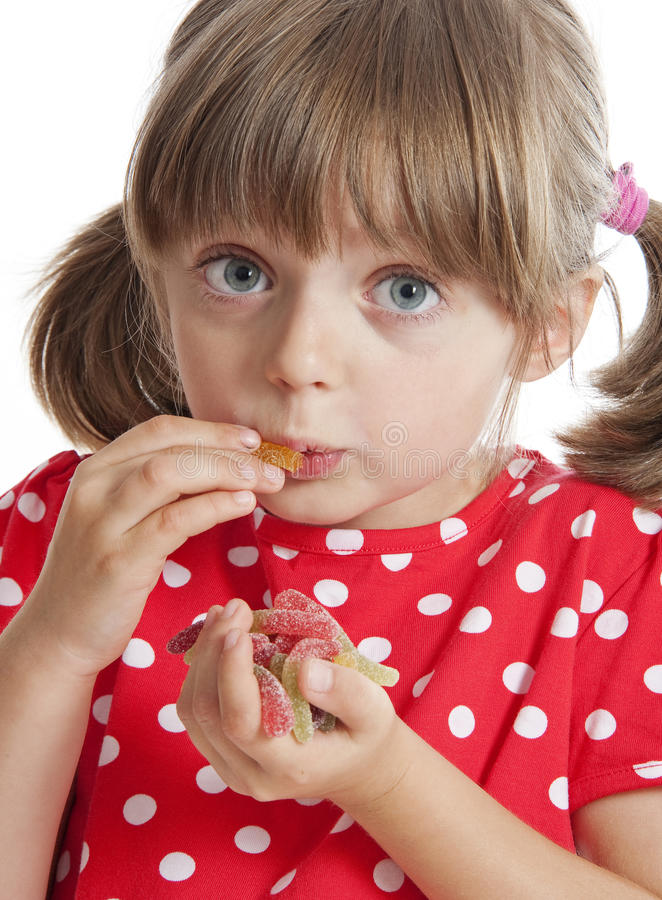 Little girl eating gelatine sweets. White background royalty free stock photo