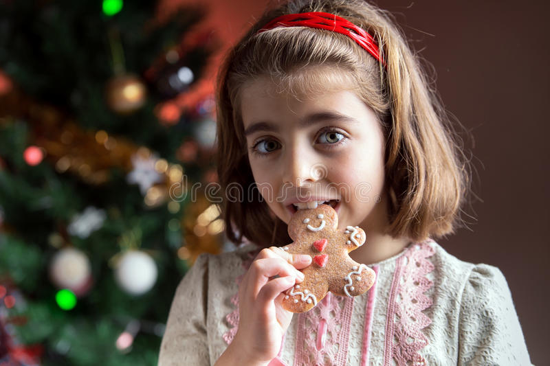 little girl eating a gingerbread cookie in front of the Christmas tree royalty free stock photography