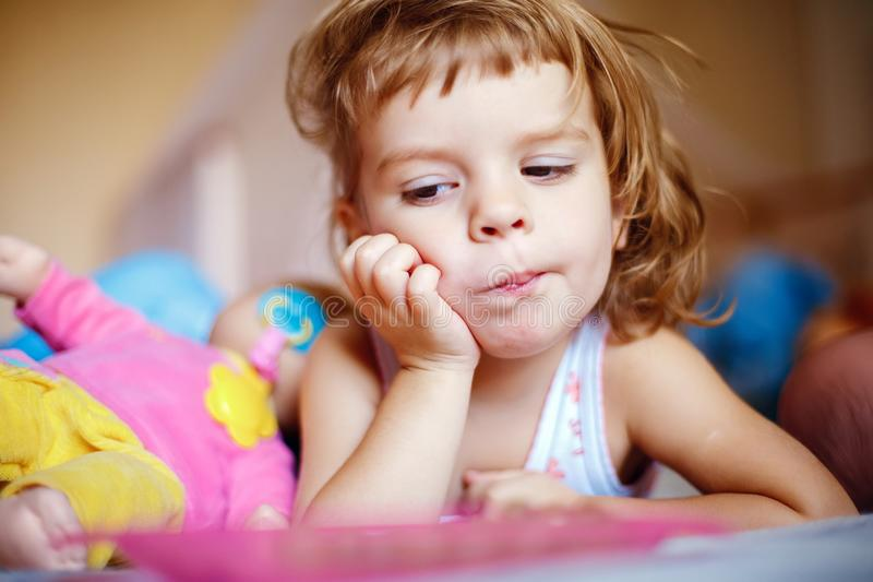Little girl eating grapes on bed stock photos