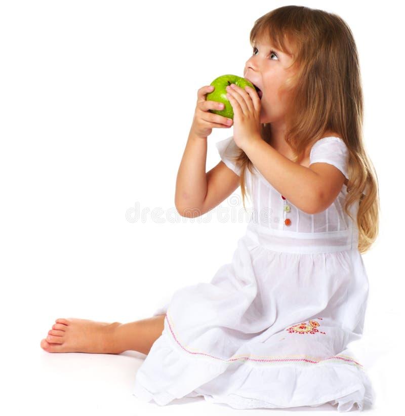Little girl eating green apple royalty free stock photo