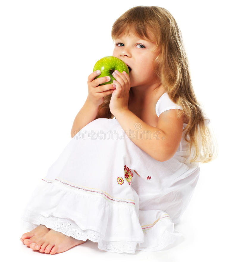 Little girl eating green apple royalty free stock photos