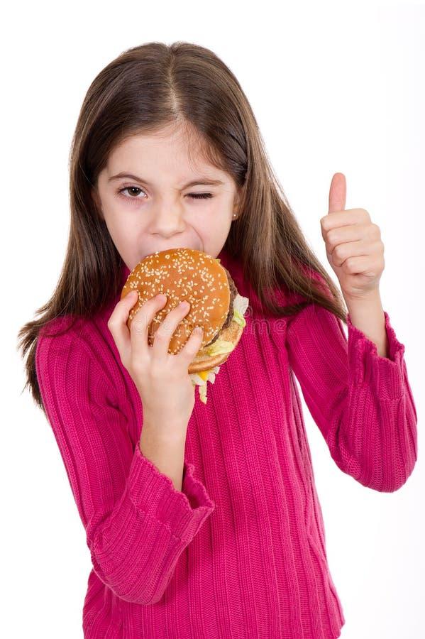 Little girl eating hamburger royalty free stock photography