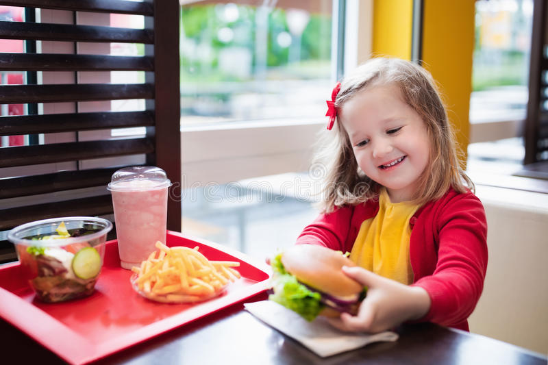 Little girl eating a hamburger in fast food restaurant royalty free stock images