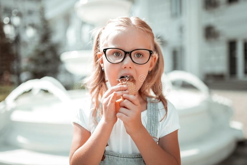 Little girl eating her chocolate ice-cream cone. stock photography