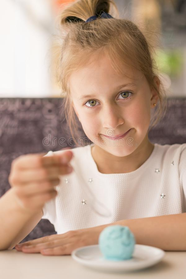 Little girl eating ice cream in a cafe. Adorable little girl eating ice cream at summer. Happy girl eating ice cream in cafe. stock photo