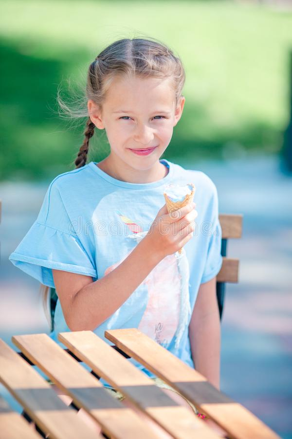 Little girl eating ice-cream outdoors at summer in outdoor cafe stock photography