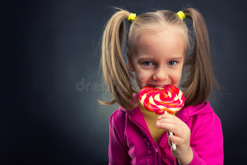 Little girl eating lollipop stock photo