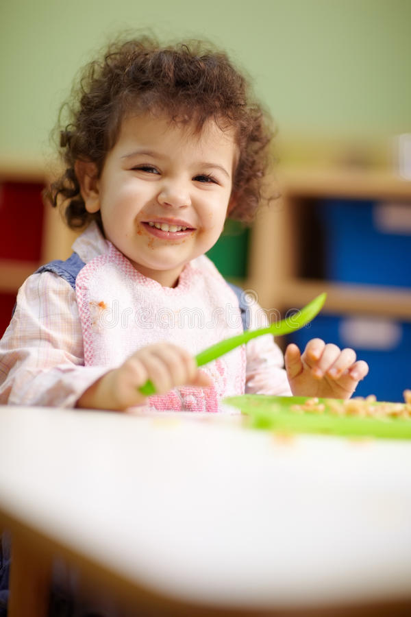 Little girl eating lunch in kindergarten royalty free stock images