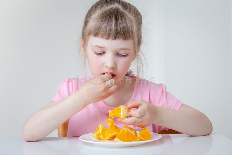 Little girl eating orange stock images